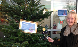 Anne Barker placing her star on the tree at Epsom Hospital