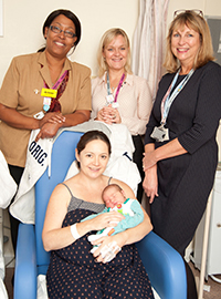 Chief Nurse and Baby Friendly Guardian Arlene Wellman, Director of Midwifery and Gynaecology Maron Louki, and Infant Feeding Lead Sue Taylor with a new mum and baby